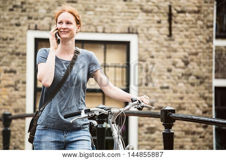 Lifestyle - Woman With Bicycle On The Phone