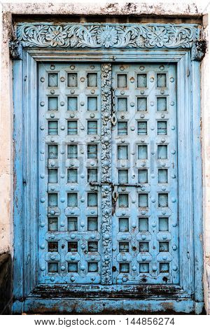 big carved wooden door with blue peeling paint on african street