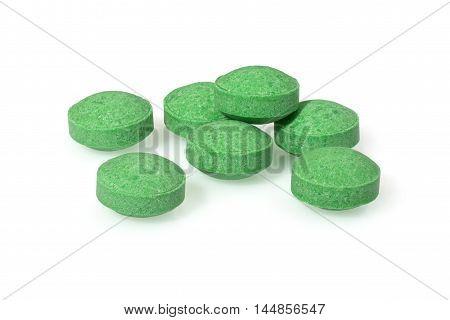 Green pills circle shape close up macro photography drug on white background