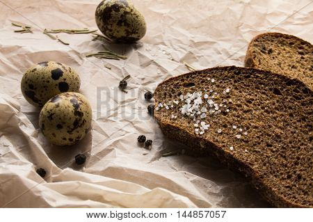 Rye bread, salt and quail eggs on a paper