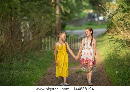 Two little girls by the handle, walk through the Park.