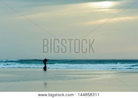 the silhouette of a dog and a young caucasian man in the distance taking a picture in front of the sea at sunset, with a cloudy sky