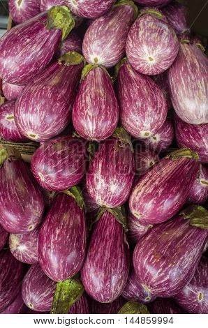Organic variegated eggplant background at local farmers market