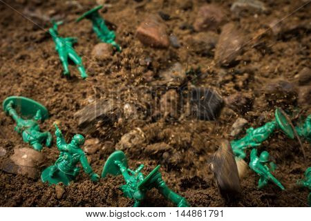Many green toy soldiers wounded by explosion on battlefield