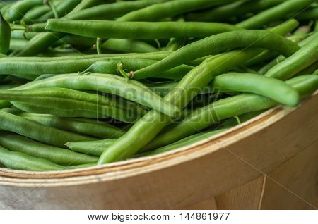 Fresh organic green beans in display basket at local farmers market
