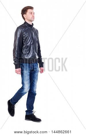 Back view of going handsome man. walking young guy. Curly guy in a black leather jacket is proudly raising his head.