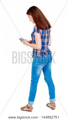 back view of standing young beautiful woman using a mobile phone or tablet computer. girl watching. Girl in plaid shirt looks into the phone.
