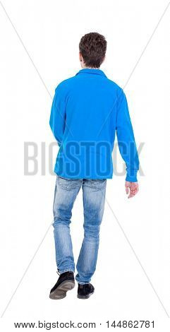 Back view of going handsome man. walking young guy . Curly boy in a warm blue sweater walking waving his arms.