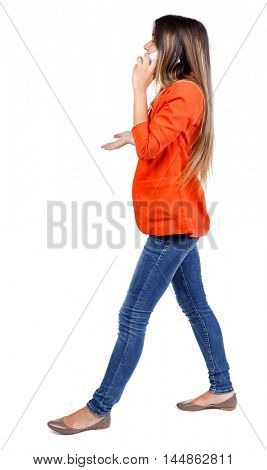side view of a woman walking with a mobile phone. back view of girl in motion. girl in a red jacket goes sideways gesticulating and talking on the phone.