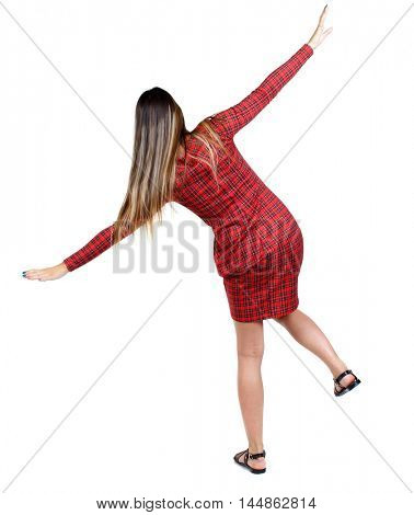 Balancing young woman. Isolated over white background. The girl in red plaid dress balancing on his leg.