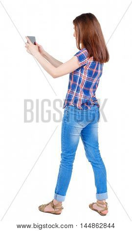 back view of standing young beautiful woman using a mobile phone. girl watching. Girl in plaid shirt standing sideways and looking at the tablet PC.