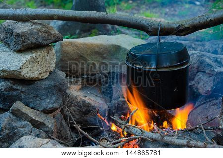 fire burns in the campaign. pot of tea by the fire. pot heated on fire. smoke from forest fire. smoke from a wild fire.