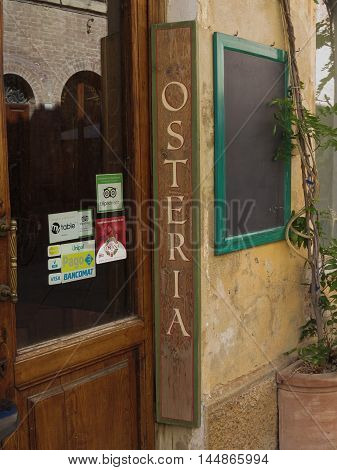 BUONCONVENTO ITALY - CIRCA JULY 2016: Osteria (meaning Inn) insignia on the street