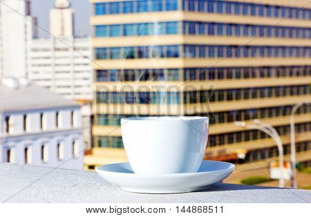 on the background of buildings on the balcony with a cup of tea coffee