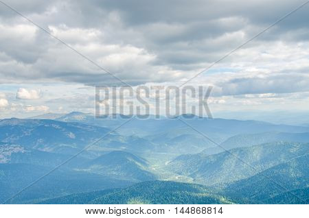 wavy colorful mountains. motley mountains. in the high mountains clouds float. Cumulus clouds.