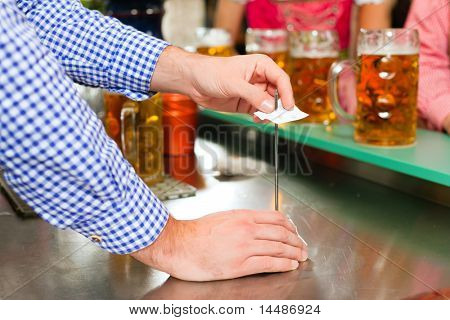 Waiter � only hands to be seen - in a Bavarian pub taking orders