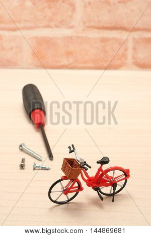 Miniature bicycle and maintenance tools on wood.  Concept of bicycle maintenance.
