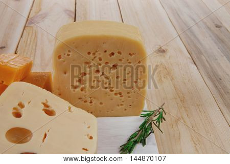 various types of fresh raw aged delicatessen cheese on white plate over light wooden table cheddar edam swiss