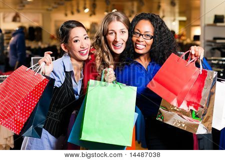 Group of three women - white, black and Asian �¢�?�? shopping downtown in a mall
