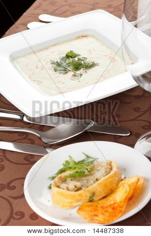 spinach cream soup with potato chips and fish pie