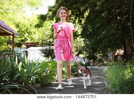 Young woman walking dog on walkway in park