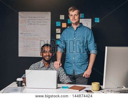 Portrait of a young entrepreneur standing with his hand on the shoulder of a colleague working on a laptop at a desk in an office