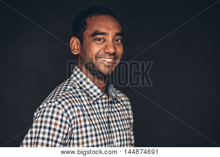 Studio portrait of a confident young entrepreneur standing crossed in front of a dark background