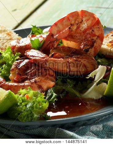 Snack with Big Grilled Shrimps Fresh Crunchy Greens Sauces and Roasted Bread Slices on Grey Plate closeup on Wooden background against Light