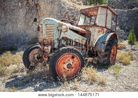 Old Abandoned Rusted Tractor Stands On Grass