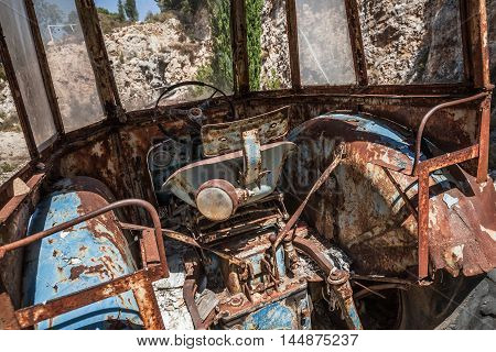 Old empty abandoned rusted tractor cabin interior