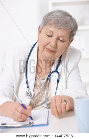 Senior female doctor, working at desk, writing notes.?