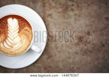 Cup of cappuccino with perfect latte art on the table. Top view, macro.