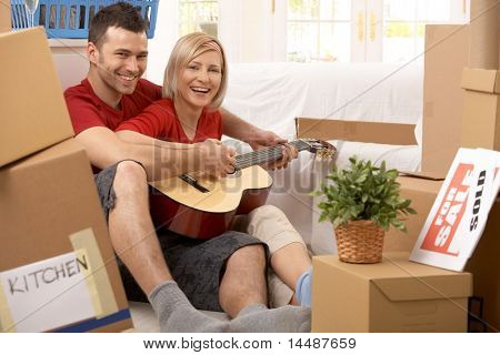 Happy couple playing guitar together in new house surrounded with boxes after moving.?