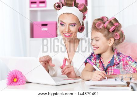 portrait of happy  Mother and little daughter in hair curlers with laptop  at home