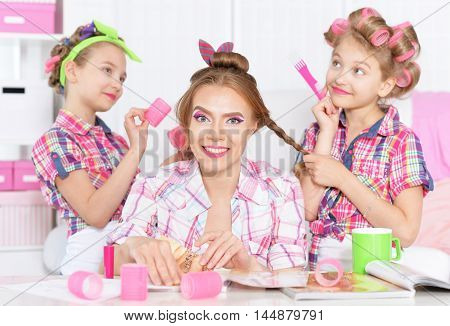 Cute  tweenie girls with mother   in hair curlers  doing hairstyle for their mother