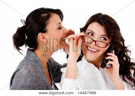 Business woman telling a secret to her co-worker while talking on the phone
