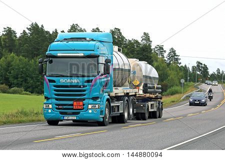 NAANTALI, FINLAND - AUGUST 5, 2016: Turquoise Scania R490 tank truck for ADR transport on the road in South of Finland. The modern truck has a bar of bright led lights as additional lighting accessories.