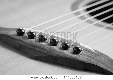 Still life photo by acoustic guitar bridge pins and saddle