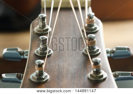 Acoustic guitar head stock and tuner select focus