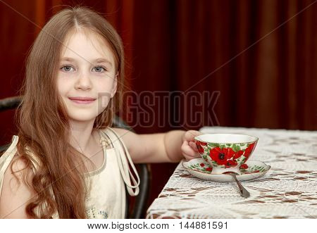 Cute little girl with long brown hair to her waist . Girl sitting on an old Vienna chair with a Cup of tea