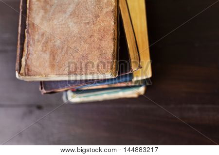 Stack of old vintage books on brown wooden background, selective focus and shallow dof.