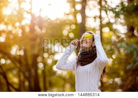 Woman In White Woolen Knitted Sweater In Autumn Forest