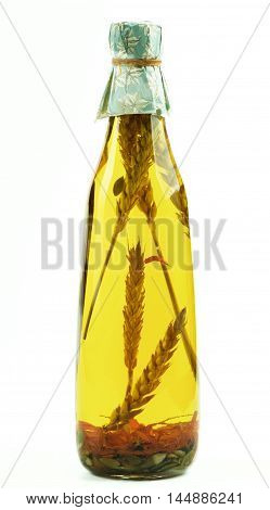 Bottle of Handmade Olive Oil with Stems of Cereals Herbs and Pumpkin Seeds isolated on White background