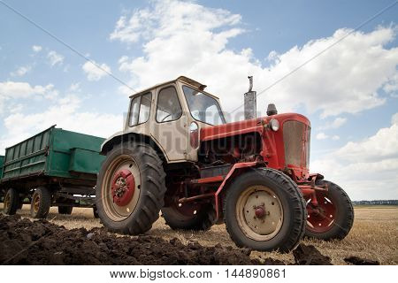 old tractor in field against a cloudy sky