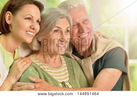 Happy senior parents with daughter at home