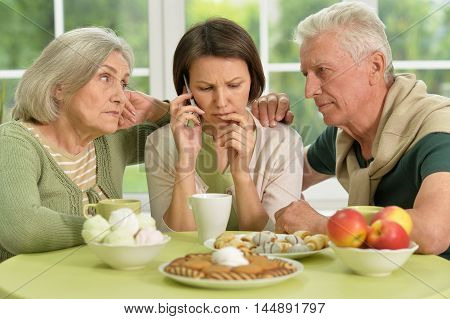 Senior parents with worried daughter at home