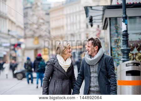Senior Couple On A Walk In City Centre. Winter