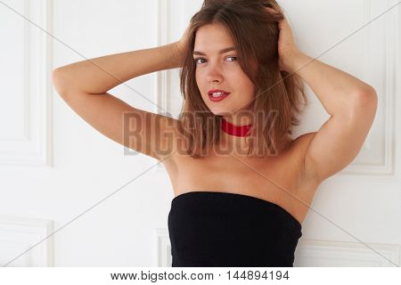 An elegant model with a flirtatious look is posing with her hands on hair. This is the another way to look brilliant on the photo