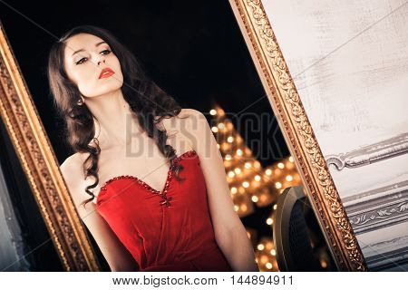 Black haired woman in red evening gown seated before full length mirror looking at reflection