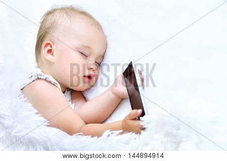 cute Sleeping baby girl  with smartphone in bed